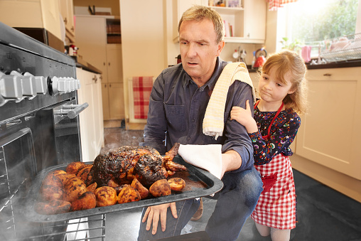 a mature man pulls the chicken or turkey out of the oven only to find it burnt and ruined. His little daughter consoles him.