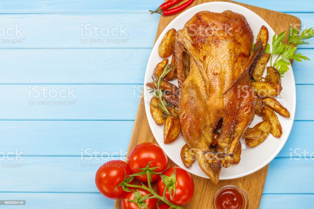 Roast duck on a white platter. Ready to serve poultry. Table setting. Roasted duck on the grill. royalty-free stock photo