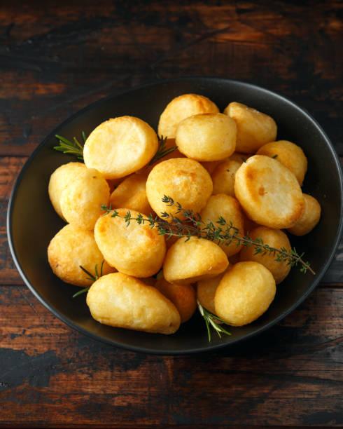 goldene röstkartoffeln gewürzt mit salz, knoblauch, rosmarin und thymian auf rustikalen hölzernen hintergrund - gänsefett stock-fotos und bilder
