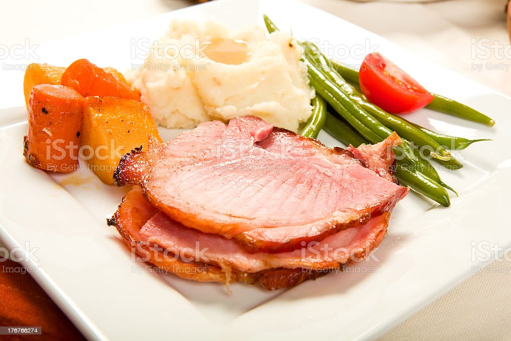 A roast ham dinner with vegetables stock photo
