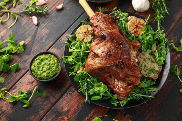 Roast Lamb leg with mint sauce, rosemary and garlic. on black plate, wooden table stock photo
