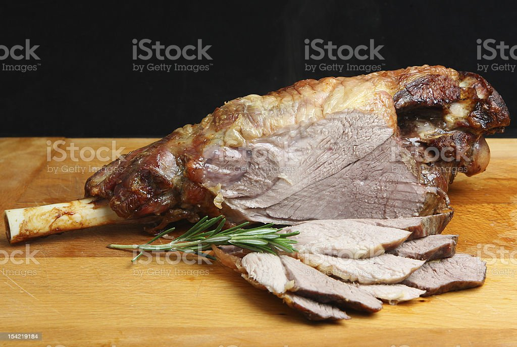 Roast leg of lamb sliced on a wooden board with rosemary royalty-free stock photo