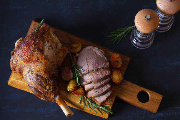 Pata asada de cordero con patatas y romero al servir tabla de madera - foto de stock