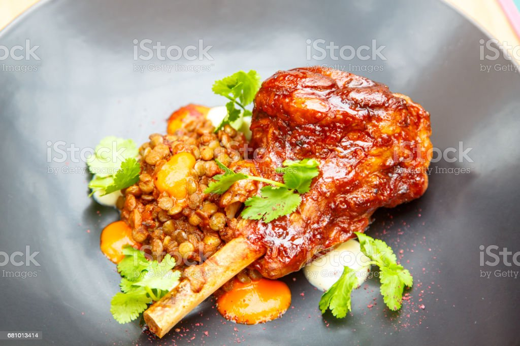Roast leg of pig or lamb with lentils on a plate. royalty-free stock photo
