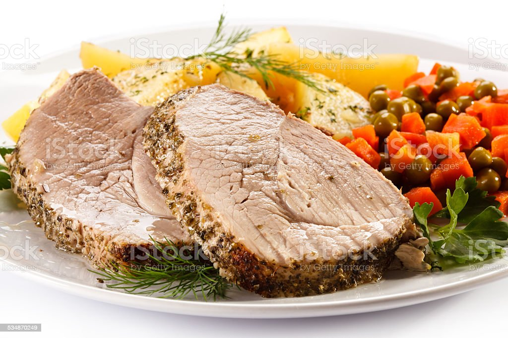 Roast meat, baked potatoes and vegetables stock photo