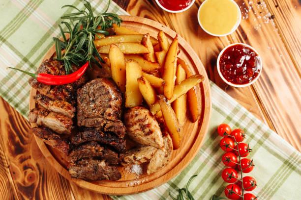 Roast Meat Steaks Fried Potatoes Wooden Board stock photo