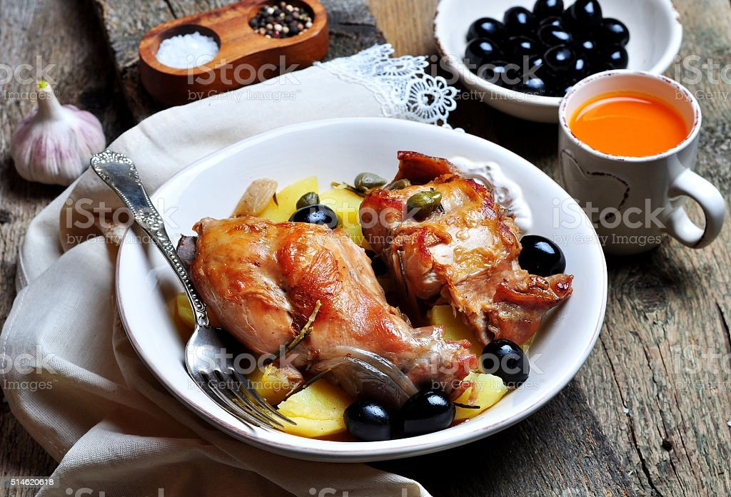 Roast rabbit in white wine with rosemary, olives and capers stock photo