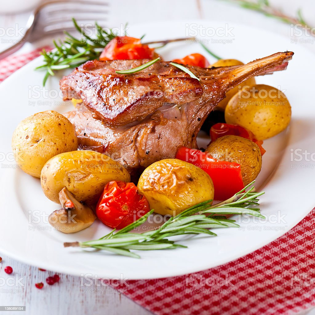Roast rack of veal with baked vegetables and rosemary stock photo