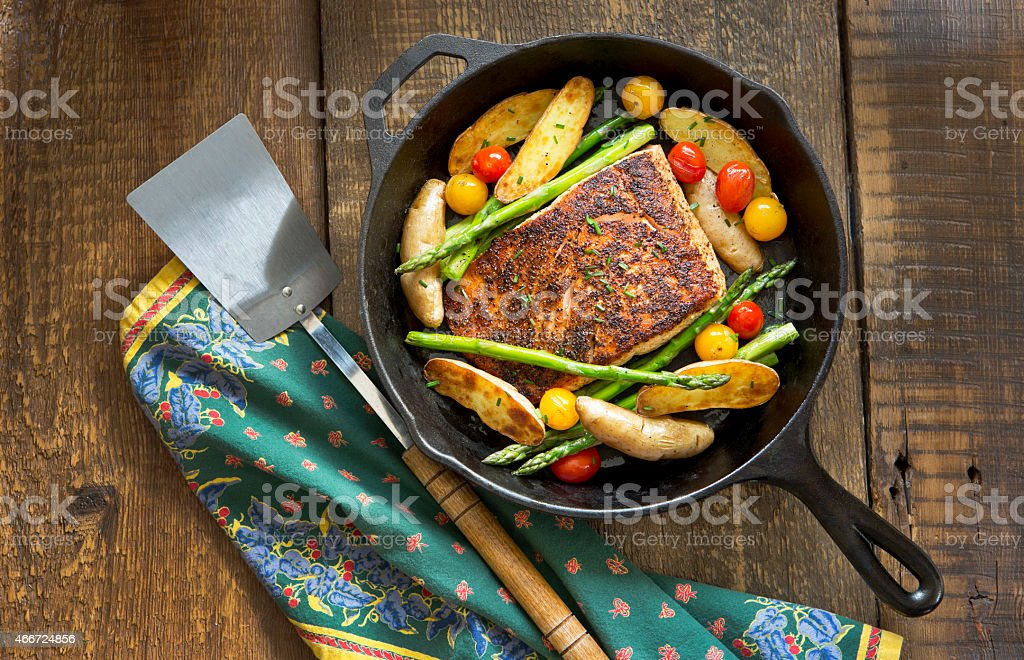 Roast Salmon and Vegetables in a Cast-Iron Pan. stock photo
