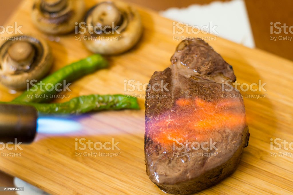 roast steak with blowtorch stock photo