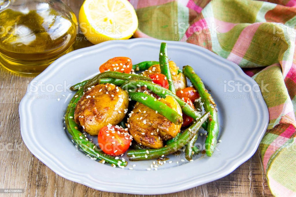 Roast vegetables in wok, potatoes, green beans, cherry tomatoes, sesame seeds, tasty vegetarian lunch on grill royalty-free stock photo