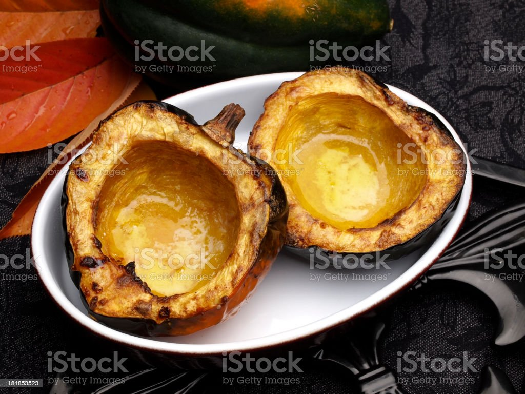 Roasted acorn in white bowl on dark setting background stock photo