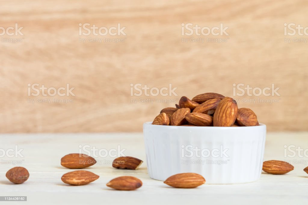 Roasted Almonds in white porcelain bowl on white wooden table
