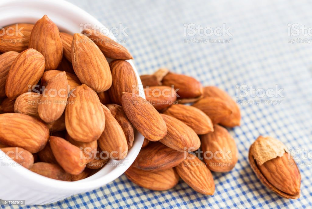 Roasted almonds, salt in bowl of white on the tablecloth. Almonds are...