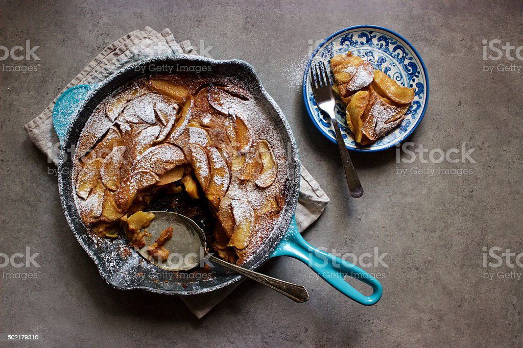 Roasted apple clafoutis (French custard cake) in cast iron pan stock photo