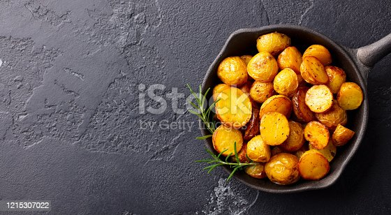 Roasted baby potatoes in iron skillet. Dark grey background. Copy space. Top view.
