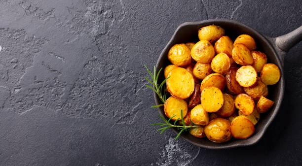 Roasted baby potatoes in iron skillet. Dark grey background. Copy space. Top view. stock photo