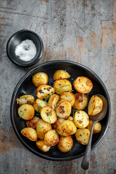 Roasted baby potatoes with wholegrain mustard and rosemary.  Rustic black dish over timber background. stock photo