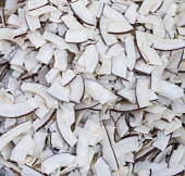Roasted baked toasted Natural Thin Sliced Coconut Chips Background texture White chopped coconut with dried slices.