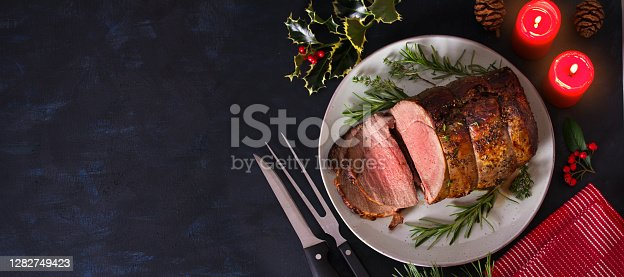 Roasted beef. Christmas decorations. New Year dinner table. View from above, top studio shot, copy space