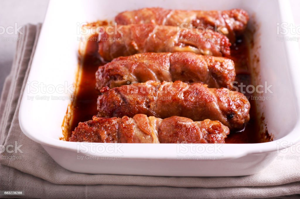 Roasted beef sausages wrapped in bacon strips royalty-free stock photo