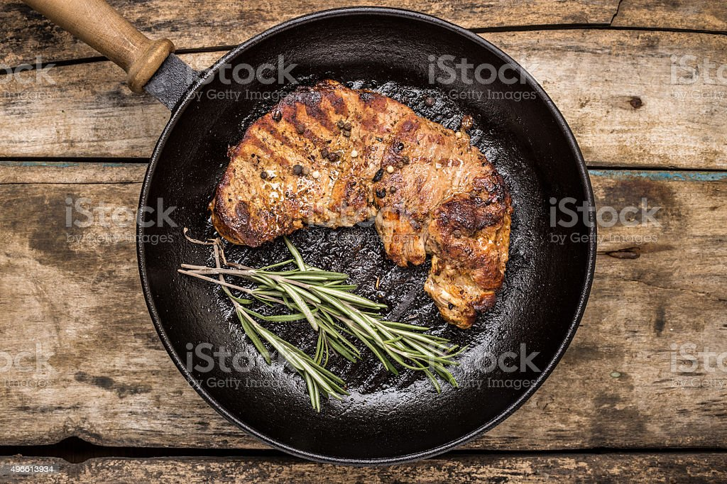 Roasted beefsteak with bunch of rosemary on grill pan stock photo