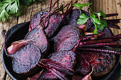 Homegrown roasted beets and garlic in cast iron skillet, fresh parsley herbs on wooden rustic table, plant based food, local produce, close up. Organic vegetables,  healthy  vegan eating, harvest time