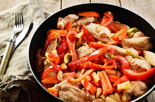 gebratene paprika in einer frittieren pfanne und besteck - paprika hähnchen stock-fotos und bilder