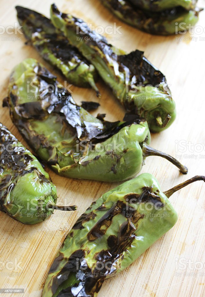 Roasted Blistered Green Chiles on Wooden Cutting Board stock photo