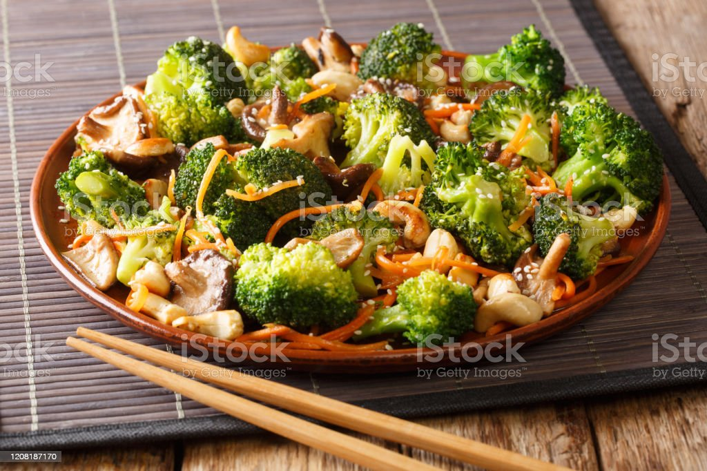 Roasted broccoli salad with shiitake, carrots and cashew nuts close-up in a plate. horizontal Roasted broccoli salad with shiitake, carrots and cashew nuts close-up in a plate on the table. horizontal Asian Food Stock Photo