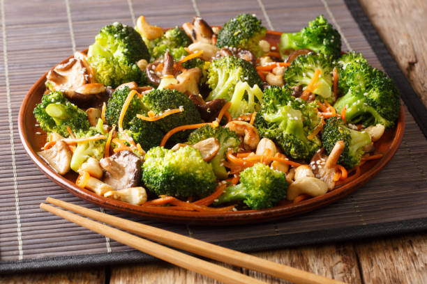 Roasted broccoli salad with shiitake, carrots and cashew nuts close-up in a plate. horizontal stock photo