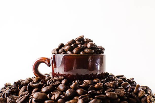 Roasted brown coffee beans & mug stock photo