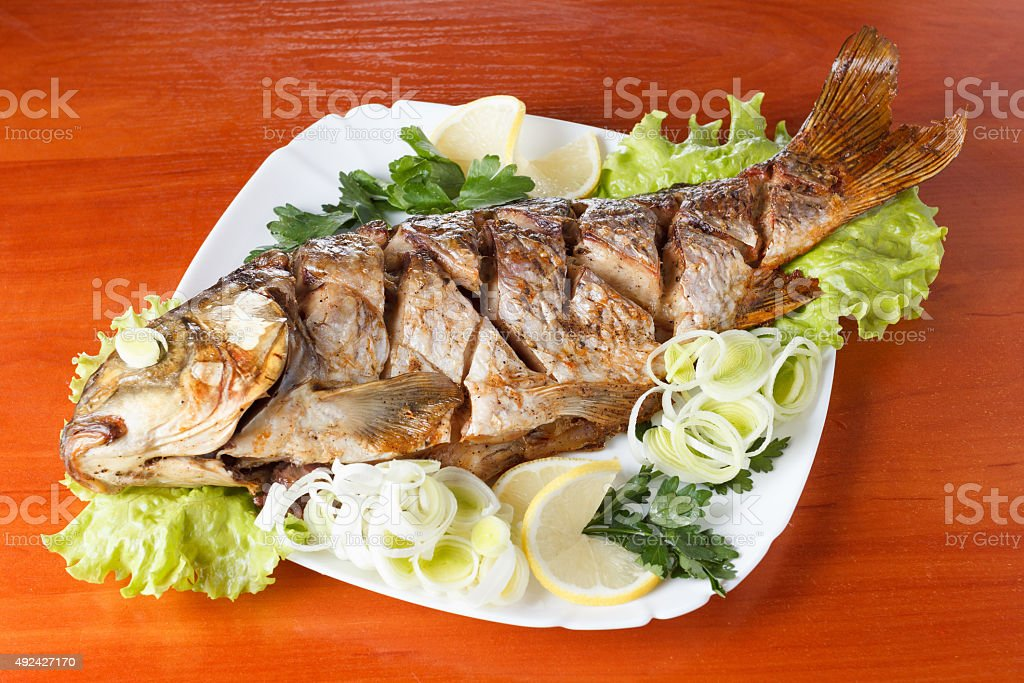 Roasted carp fish with vegetables entirely. Traditional Christmas meal. stock photo