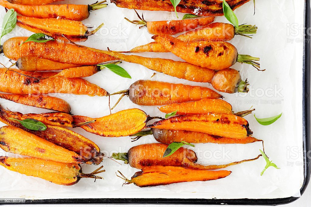 roasted carrots on white platter stock photo