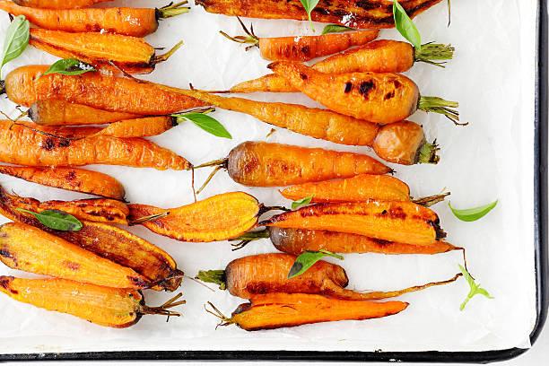 roasted carrots on white platter stock photo