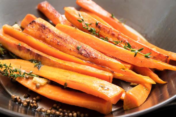 gebratene karotten mit thymian, koriandersamen und honig in einer wok-pfanne, rezept für wurzelgemüse - low carb süßigkeiten stock-fotos und bilder