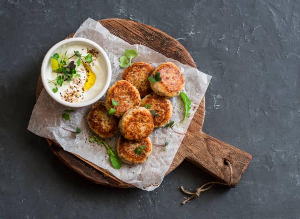 gebratener blumenkohl frikadellen und griechischen joghurt-sauce auf einem holzbrett, ansicht von oben. gesunde, vegetarische, diätetische snacks - gebackener blumenkohl stock-fotos und bilder
