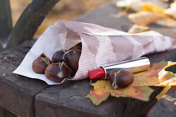 geröstete maronen und rotem lippenstift - heisse maroni stock-fotos und bilder