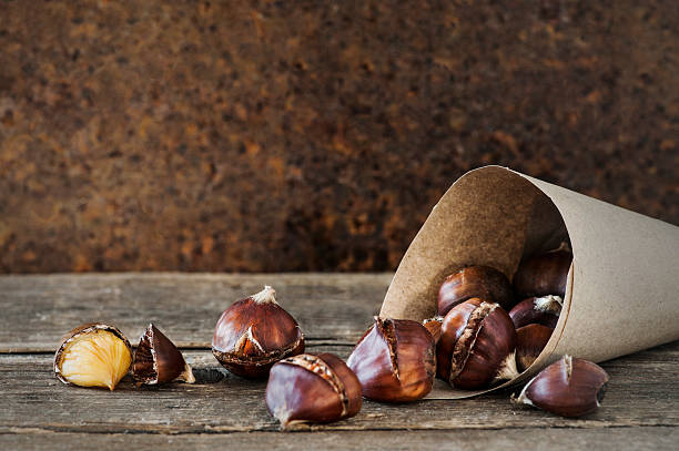 roasted chestnuts in a paper bag - heisse maroni stock-fotos und bilder