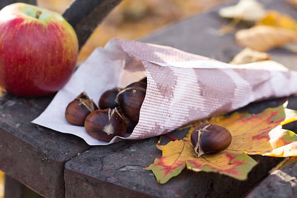geröstete maronen auf holzbank - heisse maroni stock-fotos und bilder