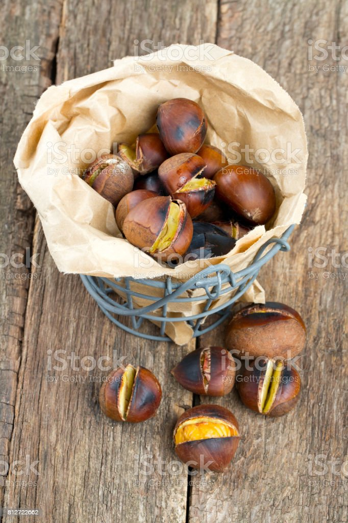 roasted chestnuts on wooden surface stock photo