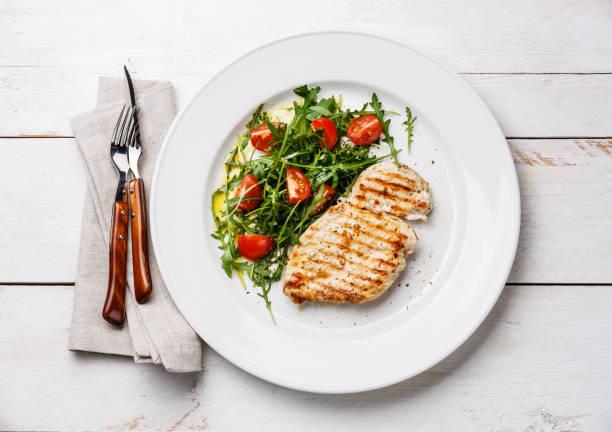 geroosterde kipfilet en frisse salade - portie stockfoto's en -beelden