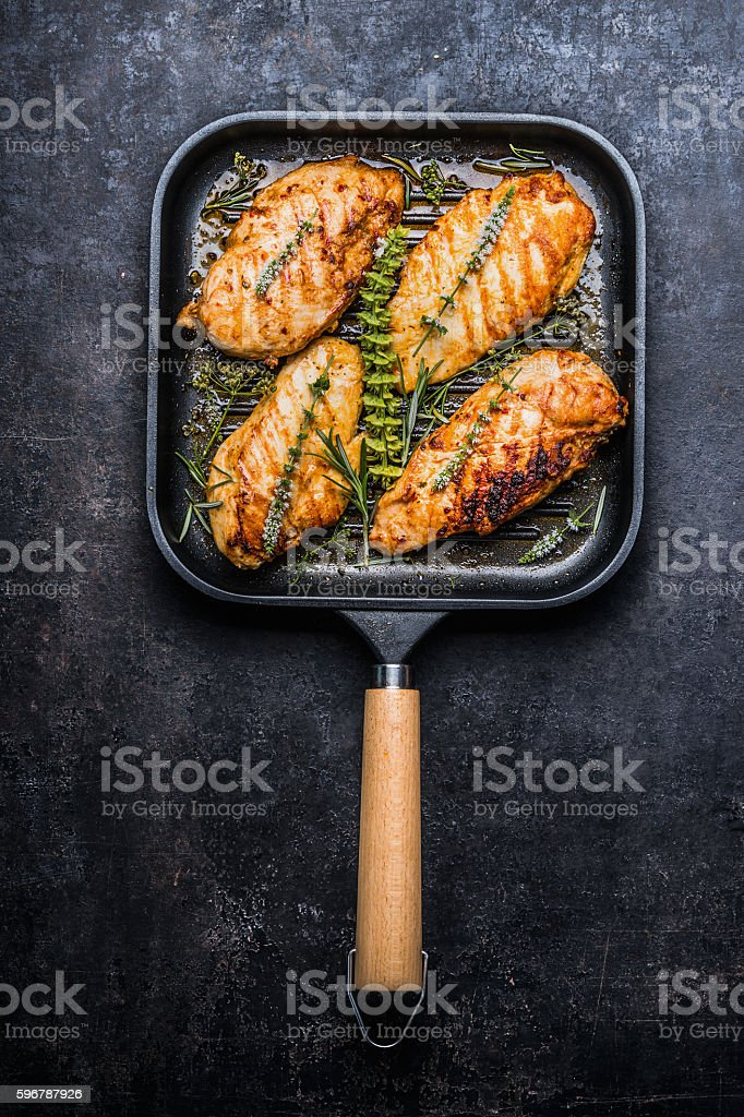 Roasted chicken breast in grill pan with fresh herbs stock photo