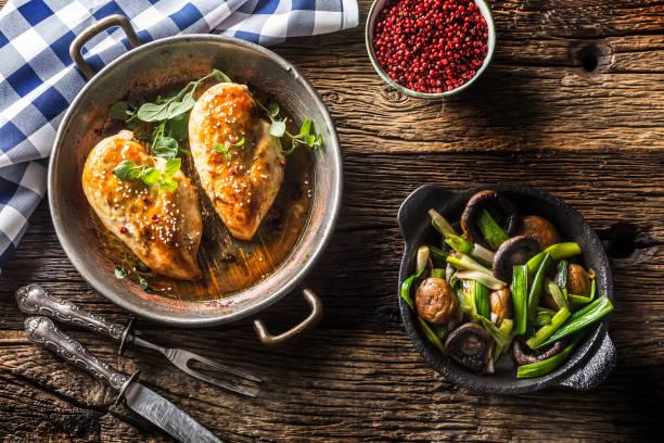 Gebratenes Hühnchen Brustesam Oregano und Pfeffer in der Pfanne mit jungen Zwiebeln und Pilz. – Foto