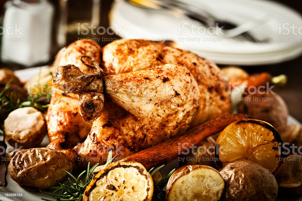 Roasted Chicken Dinner with Lemon, Potatoes, Carrots and Rosemary stock photo