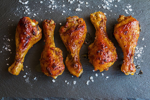 Roasted chicken drumsticks on black background. Top view. Roasted chicken drumsticks on black background. Cooked with sauce from mustard and olive oil. Top view. drumstick stock pictures, royalty-free photos & images