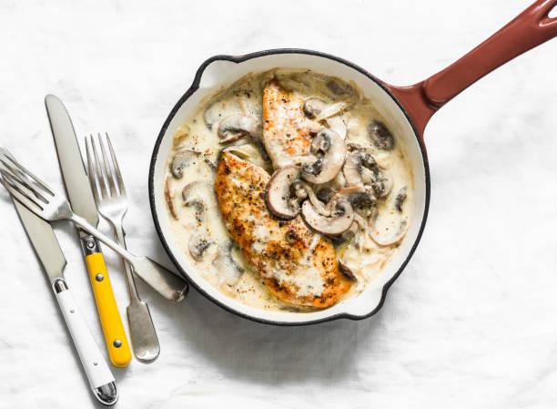 Gebratenes Hühnerfilet mit kitschigen Pilzen Sahnesauce in einer Kochpfanne auf einem hellen Hintergrund, Ansicht von oben. Köstliches hausgemachtes Mittagessen – Foto