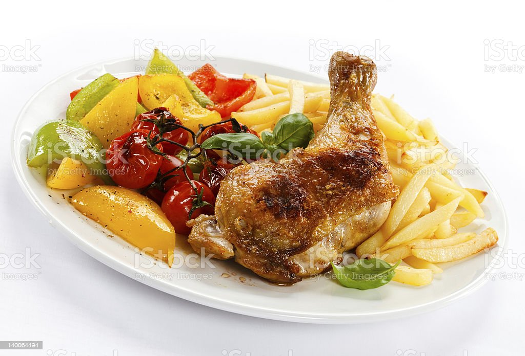 Roasted chicken leg, French fries and vegetables royalty-free stock photo