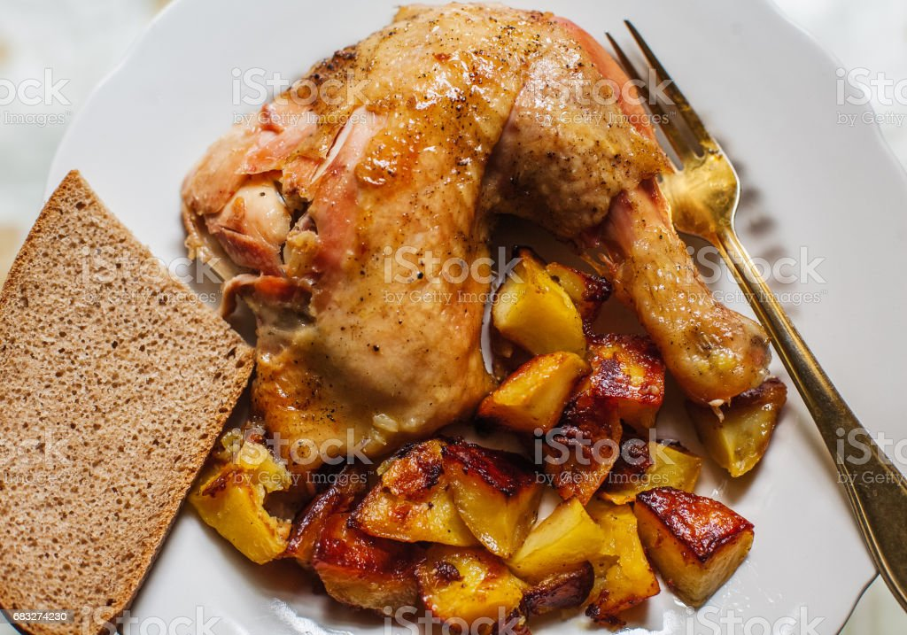 Roasted chicken leg with baked potatoes royalty-free stock photo