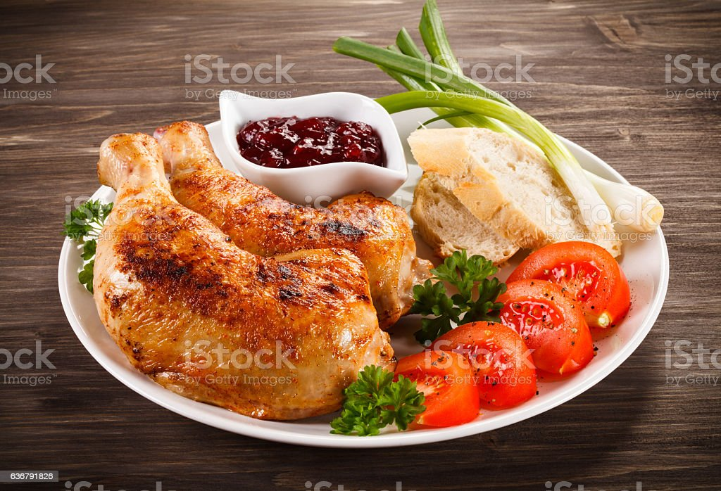 Roasted chicken legs and vegetables stock photo